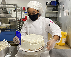 A culinary student wearing a white chefs uniform and hat and a black protective face mask spreads icing on a cake with a spatula in a Capital Region BOCES career and technical school teaching kitchen.