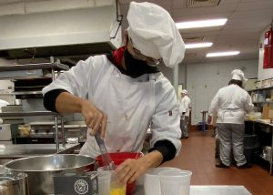 High school student Treyvon Landells, wearing a white chef's uniform and hat, eyeglasses and a protective black face mask, looks down as he uses a wisk to stir ingredientsat a workstation in a Capital Region BOCES culinary kitchen.