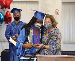Culinary graduate Melody Francis, who has long dark brown braids and is wearing a bright blue graduation cap and gown and a white and balck zig zag patterned face covering, stands at a podium and hugs teacher Deb Toy. Toy has shoulder length light brown hair and is wearing a protective face mask and floral print top. Melody was awarded 2021 Skills USA Student of the Year. A student in blue cap and gown looks on.