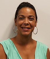 Albany Campus Career & Technical School Principal Shelette Pleat, with dark brown hair pulled back in a bun and wearing a mint green draped top, looks at and smiles for the camera.