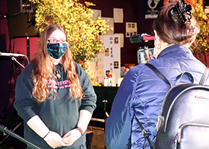 Entertainment Technology alumnus Noel Lyman, who has long light brown hair and is wearing eyeglasses, a black face mask and black hoodie with red lettering, stands on stage at Proctors Theatre in Schenectady, New York surrounded by scenery, and is interviewed on camera by a reporter from an Albany-area television station.