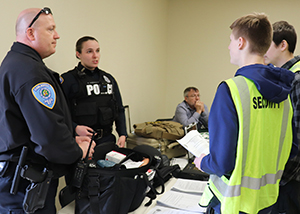Two police officers wearing dark blue uniforms stand at a table and talk to two students, who wear bright yellow vests with the words security guard printed on them.
