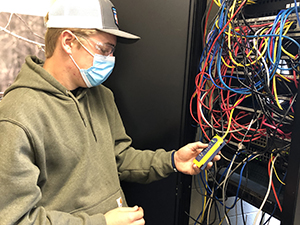 A student in the Network Cabling Technician, wearing a ball cap with a grey front and white back, clear protective eyewear, a blue protective face mask and grey hoodie, stands in front of a wall box filled with colorful wiring and takes an electrical reading with an instrument.